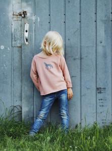 Mädchen mit Stempelmotiv Wolf auf einem rosa Lieblingspulli.