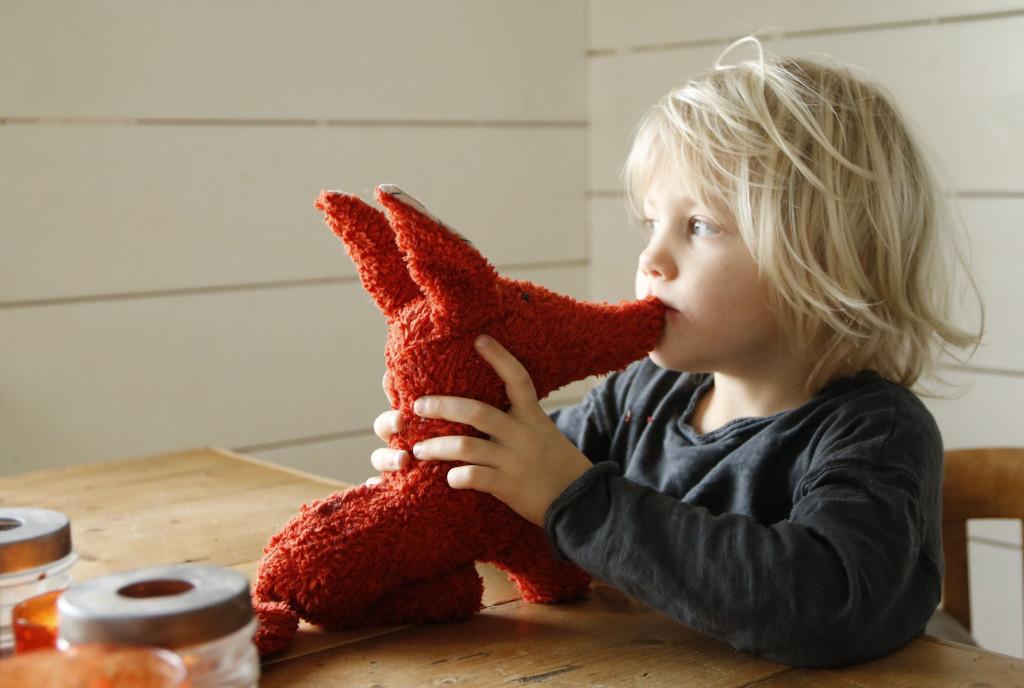 Roter Stofftier-Fuchs wird von kleinem Kind liebevoll geknuddelt.