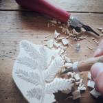 Selbstgeschnitzte, künstlerische Stempelmotive auf individuellen Kleidungsstücken und Accessoires.
