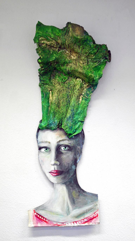 Objektcollage Frauenkopf auf Holz und Draht mit grünem Haarteil.